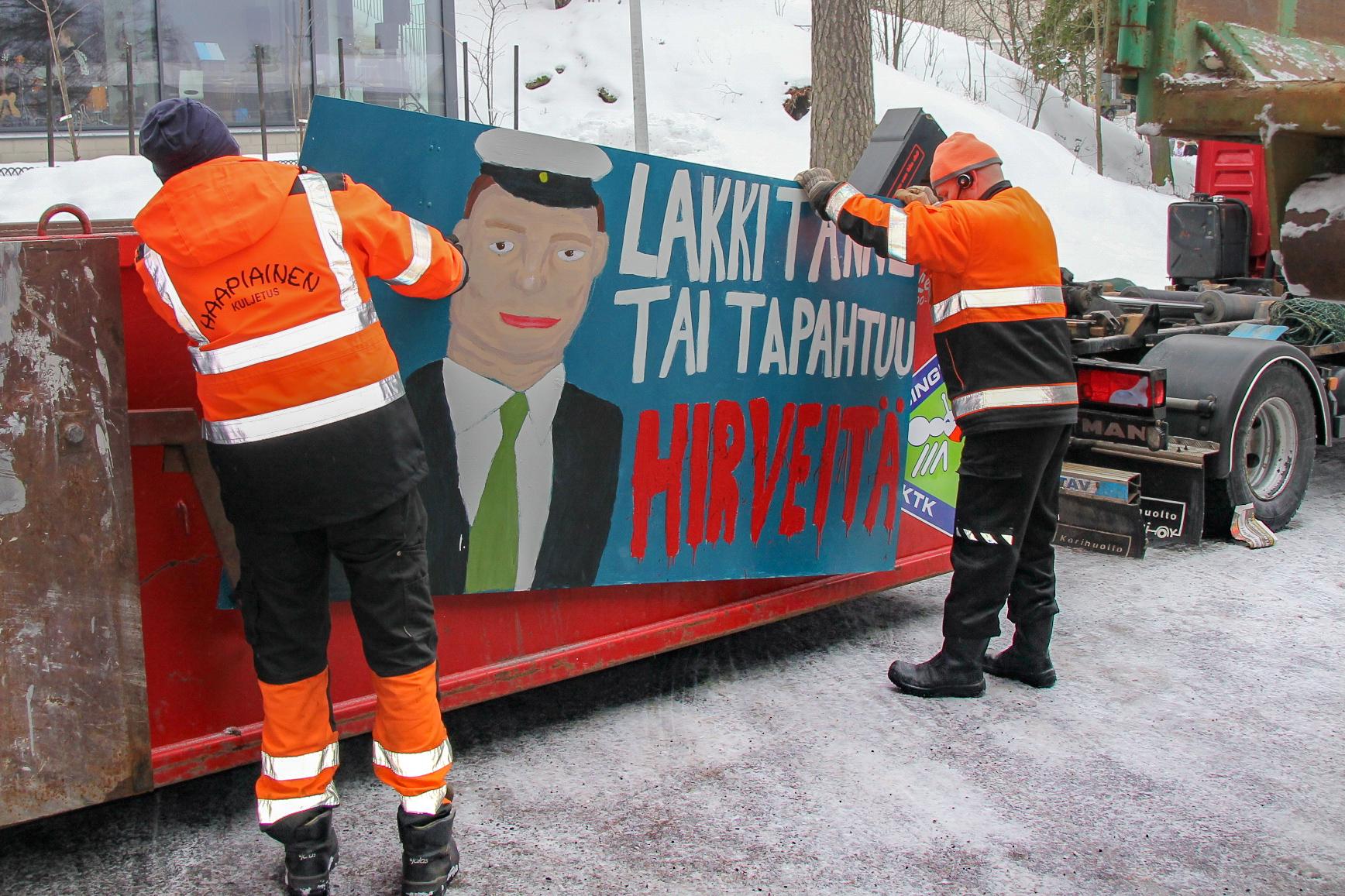 Helsingin KTK:n kuljettajat kiinnittävät abien plakaattia lavan kylkeen.