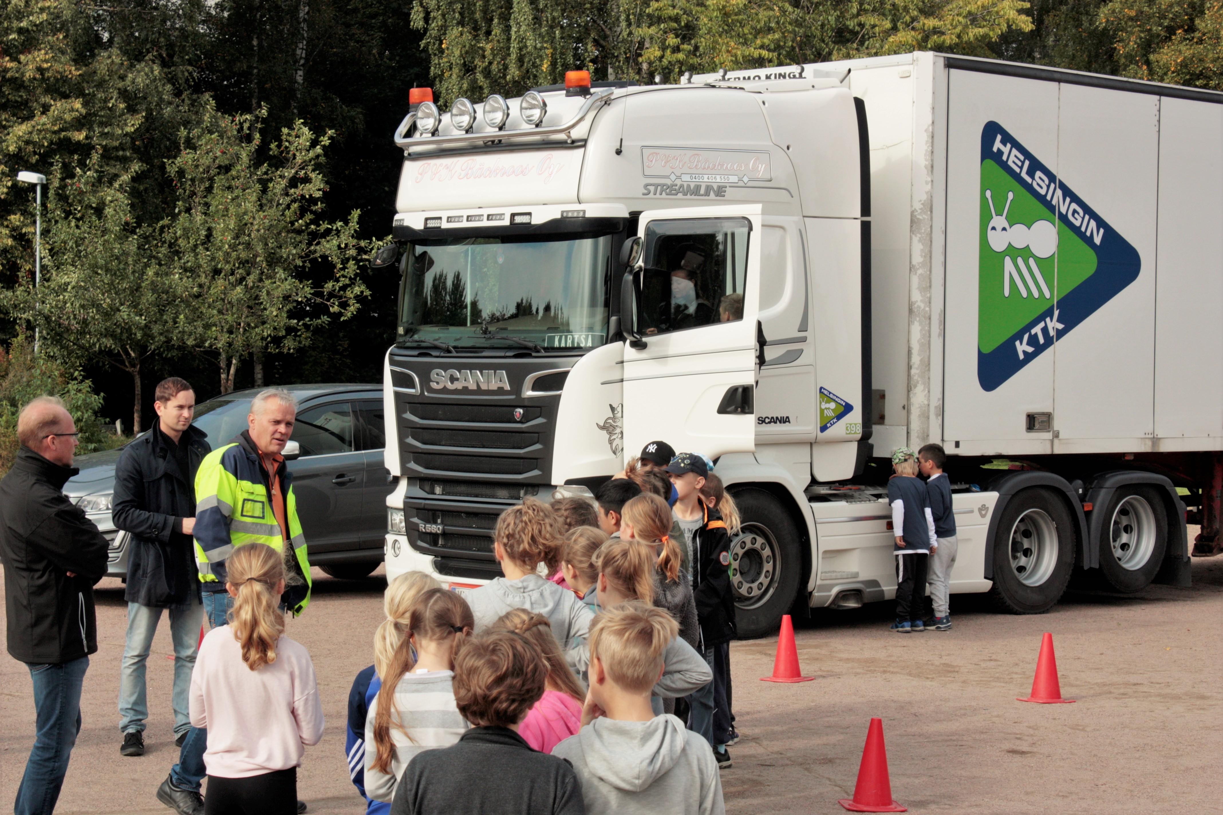 Liikennöitsijä Kari Bäckroos ja Helsingin KTK:n toimitusjohtaja Jyrki Lindroos opastivat alakoululaisia.